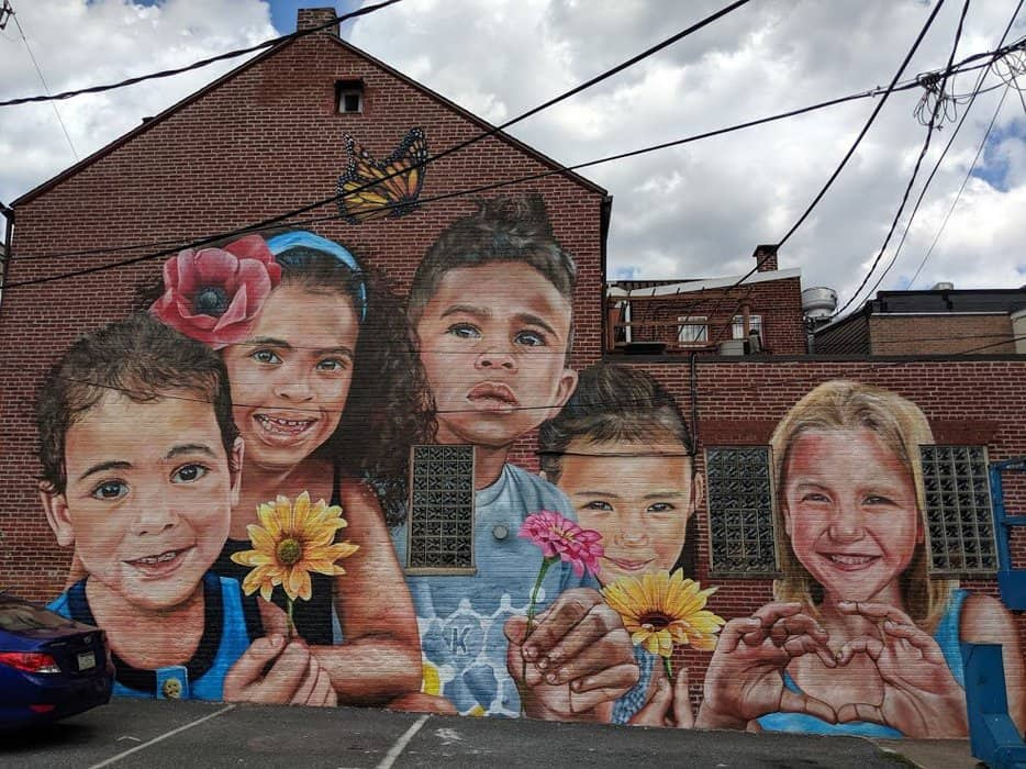 Painted by Anat Ronen, the mural at 263 Oliver Alley showcases a colorful rainbow of local children and demonstrates that love for one another transcends race.