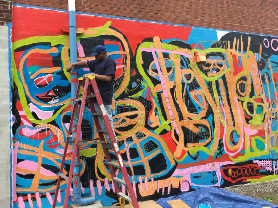 Brandon Spicer-Crawley works on his mural during Harrisburg Mural Fest. (Photo courtesy of Samantha Mitchell.)