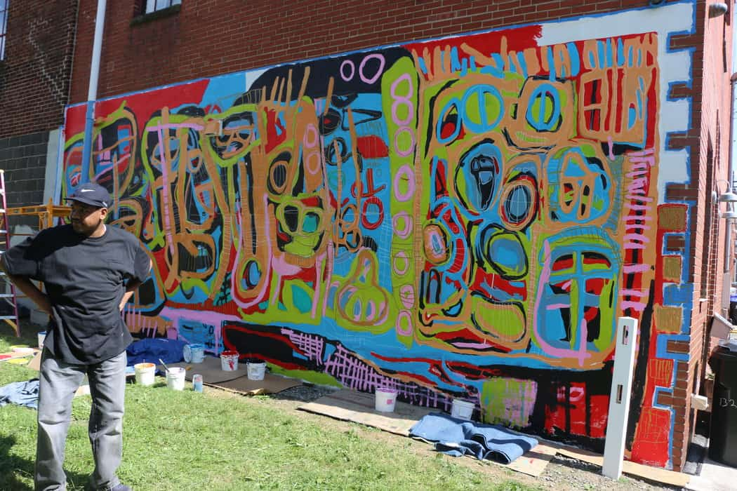 Brandon Spicer-Crawley takes a break from painting his mural during Harrisburg Mural Fest.